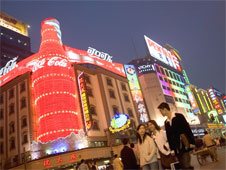 Busy Shanghai street with advertisements along the walls of the buildings. The most prominenet advert is a large lit-up Coca-cola bottle on the corner of a building.  (http://www.bbc.co.uk/schools/gcsebitesize/business/images/coke_advert.jpg)