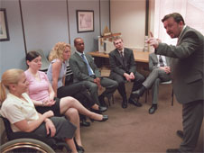 A still from the sitcom 'The Office'. David Brent welcomes new members of staff, including a lady who is a wheelchair user (http://www.bbc.co.uk/schools/gcsebitesize/business/images/staff_protection.jpg)