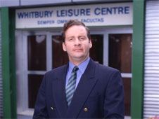 A still from the sitcom 'The Brittas Empire'. Leisure centre manager Gordon Brittas stands outside Whitby New Town Leisure Centre (http://www.bbc.co.uk/schools/gcsebitesize/business/images/staff.jpg)
